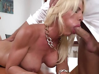 A hot blonde round large tits is doing a blow job like a pro